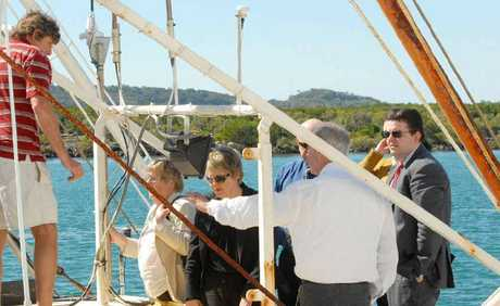 Skipper of the Guiding Star James Hicks (left) shows members of the coronial inquest team over the boat in the Pioneer River.