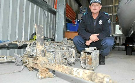 Senior Constable Murray Lyons with the remnants of a Second World War plane caught by a fishing trawler.
