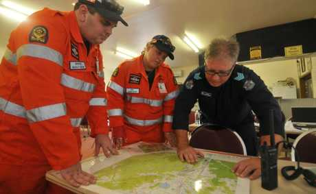 SES Mackay&#39;s Brenton Harris, SES Sarina&#39;s Sam Roempke and search co-ordinator Sergeant Marcus Brown look over maps of the area where police and SES searched for Sean Russell. 