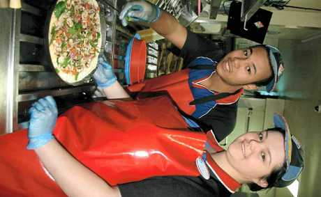 WINNING WORKPLACE: Domino's Byron Bay assistant manager Courtney Moss and employee Tawanda M'zumguleigh at work. The store has been named the happiest Domino's workplace in the nation.