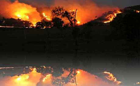 FLAMES IN THE DUSK: Minden was surrounded by fire on Friday evening. Police and QFRS investigations into the cause of the fire are continuing.