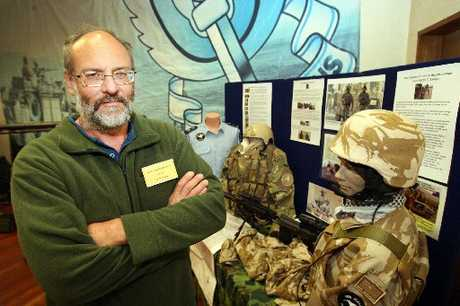SOLEMN SALUTE: The organiser of the Tauranga Arms and Militaria Show, Keith Frazer, stands in front of a memorial display to New Zealanders who have died while serving in Afghanistan.