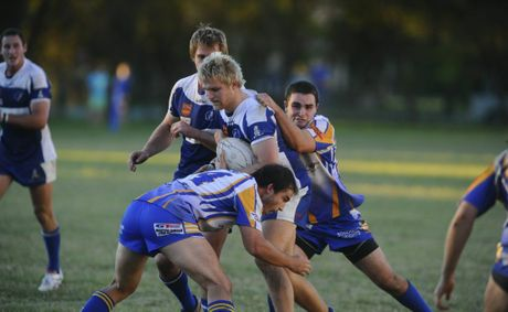 Ghosts' Sam Hartmann is grabbed by some Mustangs during round 9 NRRRL rugby league clash at McGuren Field, Grafton.