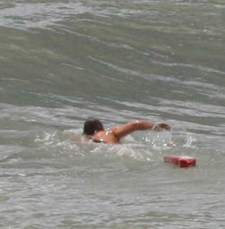 A lifeguard on his way to a swimmer in trouble.