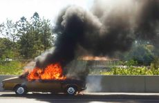 FIERY DEMISE: Fire engulfs a Holden Kingswood on the Ipswich Motorway yesterday. Photo: Rob Williams