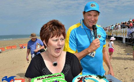 Mackay Mayor Deirdre Comerford and Mackay Harbour Beach Race Day manager Mick Pope prepare to cut a cake to mark Mackay's 150th anniversary.