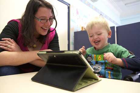 IPAD GENERATION: Dominic Johnston, 3, enjoys using an iPad with early intervention teacher Beccy Creswick at The Champion Centre, a Christchurch centre for pre-school children with disabilities.