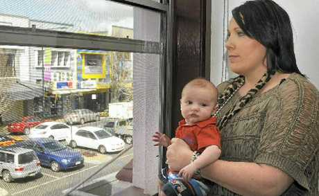 CBD resident and business owner Melita Bell holds her infant son Malakai in their Ruthven St home.