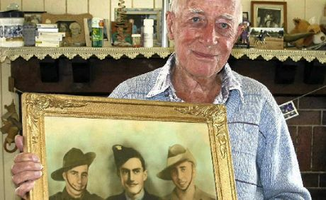 Battle of Milne Bay veteran Len Acworth with a photo of himself and two brothers during the Second World War, (from left) his twin Ernie, younger brother Syd and Len.