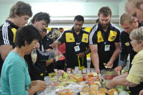 FREE FOOD: Hurricanes players assist with preparing food for Kids Kai Time in Masterton earlier this year. The programme provided free school food for children.
