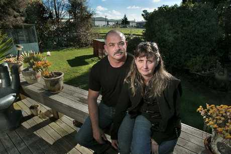 Keith and Val Gabrielle sit in fornt of a gap in the fence where the company next door on Omahu Road, Hastings. Razo Engineering wants to build a warehouse near the boundary that will effectively block out the sun.
