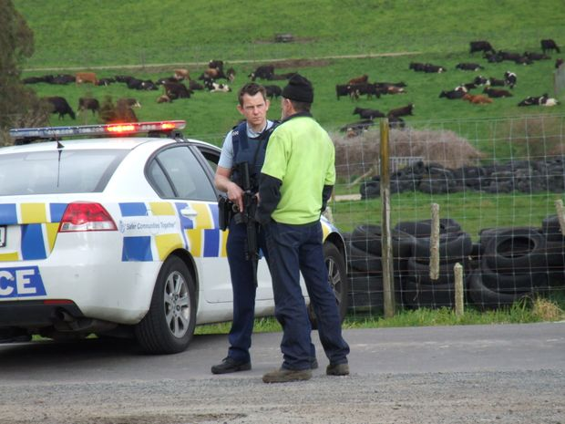 Rotorua armed police talks with a bystander during a hunting incident at Waikite Valley