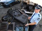 Acting Inspector Grant Marcus with the wreckage from the car crash in Burnett Heads on Thursday night.