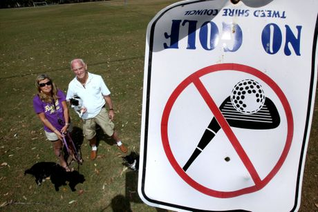 Sue Watts and George Chaoman below a sign which clearly bans golf.
