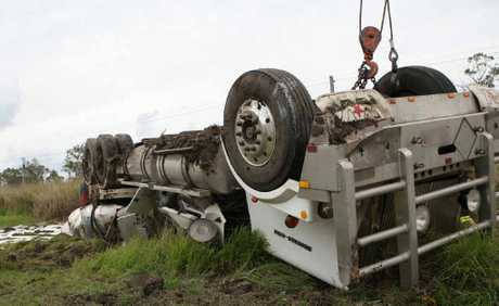A semi-trailer lies upside down on the side of the Bruce Hwy after it overturned at the Gavial Creek Rd intersection yesterday morning.
