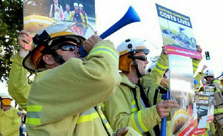 Central Region senior firefighter Greg Harris (top right) speaks about the impacts of the State Government's job cuts on urban and rural fire services abilities ahead of a bad fire season during the United Voices National Day of Action rally in Rockhampton.