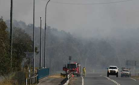 Crews attend to a bushfire on Tweed Coast Rd, Cudgen, on Friday. Its cause is now under investigation.