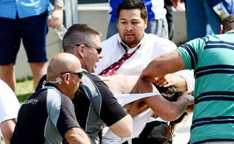 A fan is dragged away from a brawl by security staff.