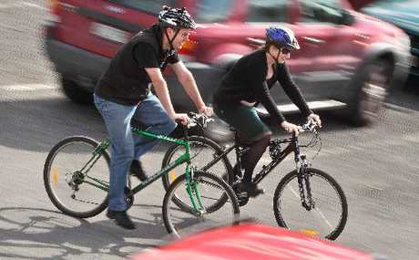 NO CARS: Workmates Greg Vincent (left) and Amanda Hunt are biking to work each day, instead of driving, as part of Car Free Week.