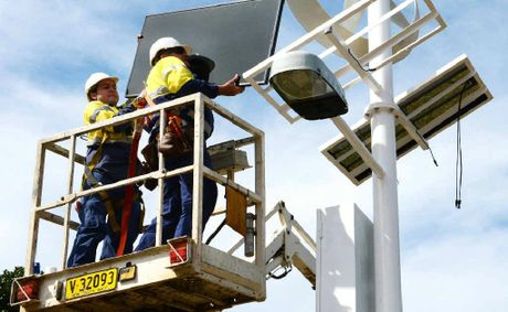 Electricians Tony Lees and John Cochrane install the solar wind-power streetlight near Lismore City Hall.