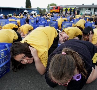 Mikayla Ashforth (left) and Meg Lindsay, Year 5 pupils at Mahora School, practise the Drop, Cover, Hold earthquake drill in preparation for the nationwide ShakeOut next Wednesday.