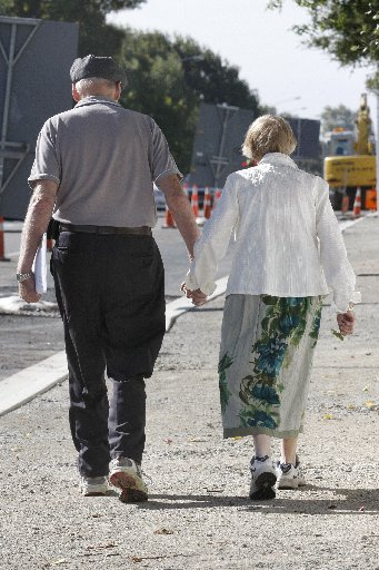 An elderly couple walk hand in hand.