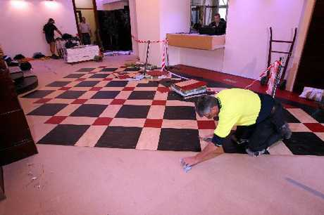 "SQUARED AWAY: Peter Brack, a flooring expert from Queensland, works on the Masonic's ""new but old"" traditional linoleum-covered foyer. PHOTO/PAUL TAYLOR HBT123098-07"