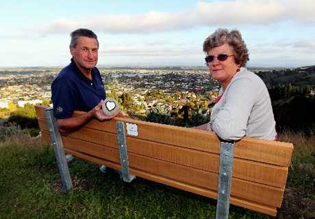 MEMORIAL: Simon and Cathy Cowan at Sugar Loaf Reserve, where they placed a commemorative seat in memory of their son Phil.PHOTO/FILE 