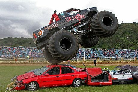 CRUSHED: Benn Milne jumps the Demon Energy Monster Truck on to a stack of wrecked cars at a recent event in Upper Hutt.
