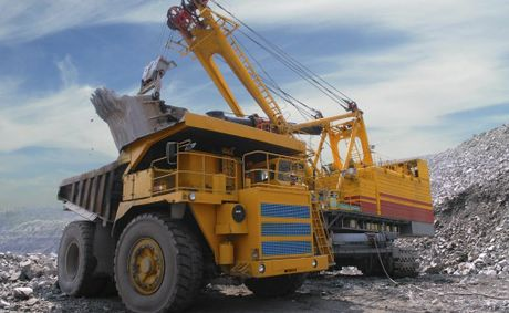 Loading of iron ore on a big dump-body truck.