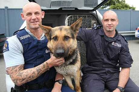 DUTY CALLED: Constable Darren Pavelka and dog handler Senior Constable Lyal Bayliss with Brock after the armed confrontation yesterday.