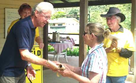 Tweed mayor Barry Longland receives a CSG-free declaration from Chillingham resident Christine McKinnon as Lock the Gate - Tweed's Michael McNamara looks on.