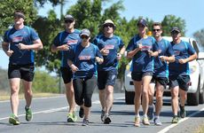RAAF airmen arrive at Amberley after running from Bundaberg to raise money for the Queensland Cancer Council.