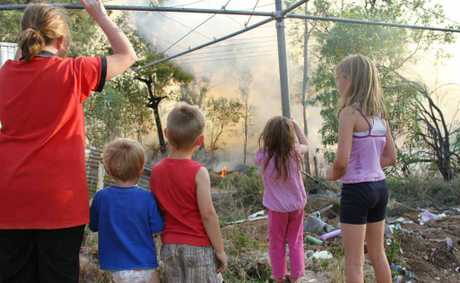 Children watch on in concern as firefighters work to protect their home.
