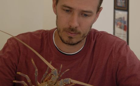 Southern Cross University PhD candidate Jesse Leland with a moulted shell from an Eastern Rock Lobster.