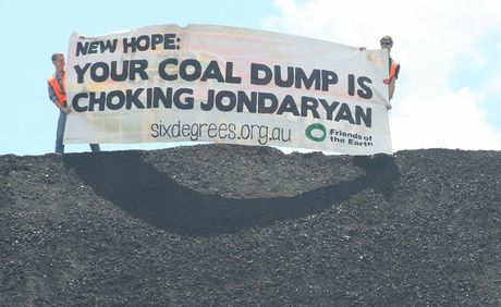 Six Degrees protestors Samuel Robb (left) and Bradley Smith unfurl a banner on top of a coal stockpile at the New Hope Group's rail loading facility at Jondaryan today.