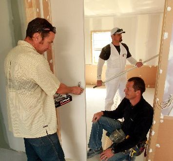 HOME STRETCH: Builders Jon Band (left) and Brendan Webb sort the doors while painter Shaun Burton sorts the first coat for the walls.