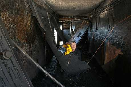 GUTTED: Teacher Michael Chemis and Harold the Giraffe, in the burnt out Life Education Trust mobile classroom Mr Chemis had used for the last nine years.