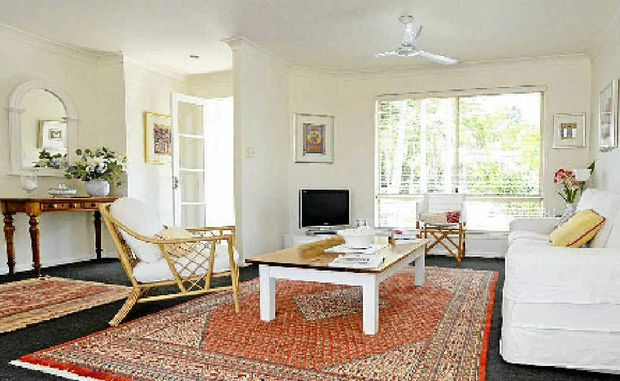 The sitting room is a light-filled, predominantly white space with colourful rugs and soft furnishings. Gowan allows a house to transform over time.