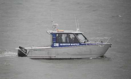 Police aboard the Tauranga Harbourmaster boat navigate the channel, helped by one of the surviving boaties. Photo / John Borren