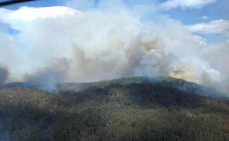Blistering winds and soaring temperatures have caused a fire to jump containment lines in dense scrub west of Woodburn this afternoon. Photo RFS.