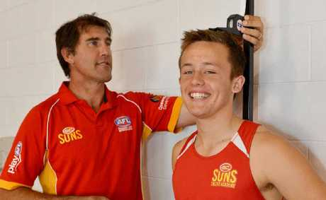 Former AFL player and member of the Gold Coast Suns development team Craig Starcevich measures up Jordan Harding.