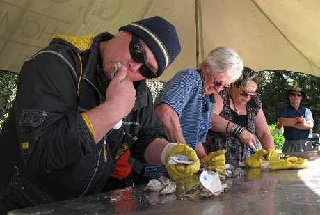 DOWN THE HATCH: Whangarei's Mike Carter (left) slurps his way to victory in the final of the oyster-shucking competition, beating Auckland's John Nixon and Bobbie Ngauma of Waipapakauri.