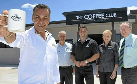 One of The Coffee Club directors John Lazarou, Landmark Harcourts principal Max Holder, franchisees Peter and Lyndall Cook and Landmark Harcourts real estate agent Peter Thew outside the doors of the new Coffee Club.