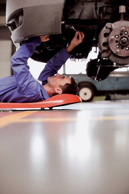 A mechanic works on a car. File image.