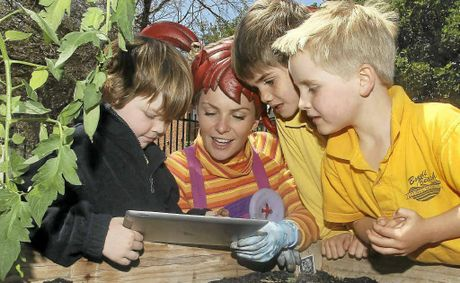 GETTING DOWN: Dirtgirl helps school children plant their own smart seeds using the dirtgirlworld app on an iPad at Bondi Beach Public School.