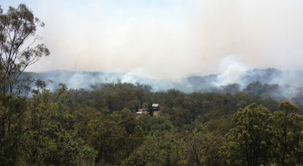 Fire threatens a home near Ravensbourne where fire authorities are back burning. Photo: Stuart Cumming/The Chronicle
