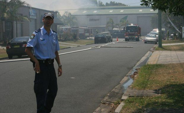 A police officer warning people away from a fire at Byron Bay&#39;s Arts and Industry Estate. Oct 26, 2012