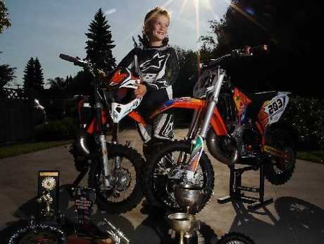 Luka Freemantle shows the difference between his 50cc motocross bike, on the left, and his 65cc one with his some of his impressive haul of 2012 trophies in the foreground.