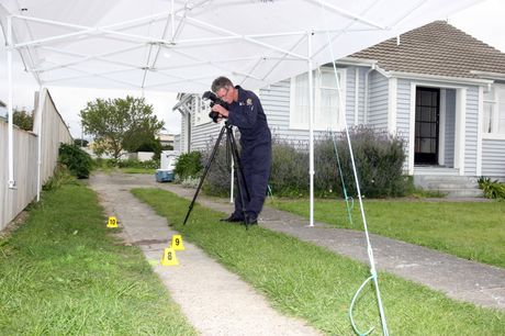 CRIME SCENE: Wairarapa police forensic photographer Bob Hooker capturing the blood stain left after a serious assault at a Martinborough home which landed local firefighter, Peter Fisher (inset) in hospital with serious head injuries.